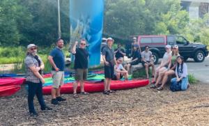 Team ready to start kayaking, one fist pumping.